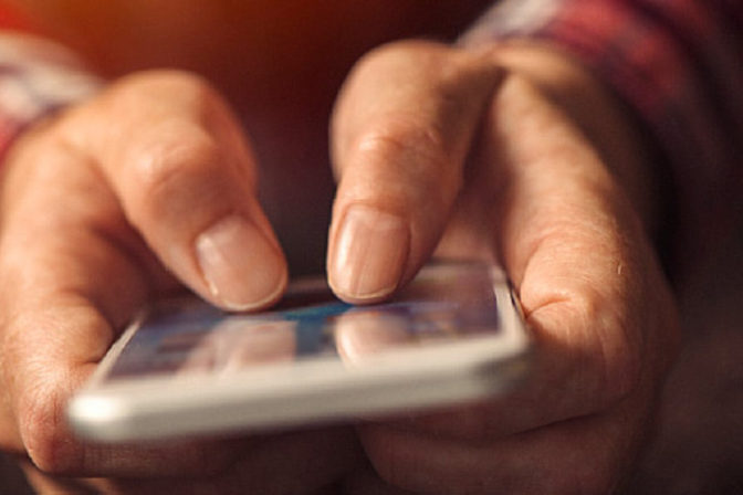 A picture focusing on handsof a man using a smart phone